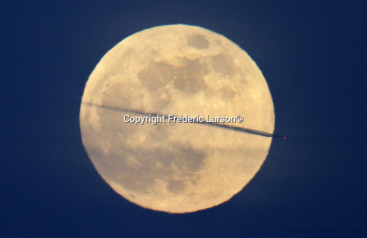 A jets contrail streaks through the June full moon as seen from the Marin Headlands on June 3, 2012.