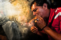 A Salvadorean 'brujo' (sorcerer) puffs a cigar to predict the future of his client from burn tobacco leaves in a street fortune telling shop in San Salvador, El Salvador, 18 February 2014. Due to the strong historical tradition of using tobacco by indigenous shamen in Americas, nowadays, the reading of tobacco is one of the most most widespread methods of divination, employed by esoteric practitioners and healers in all Latin American countries. According to the shapes of burn leaves, colors of ash and smoke, burning velocity and other factors, the experienced fortune teller interprets the manifested signs in relation with the supposed future of people involved in the tobacco ritual.