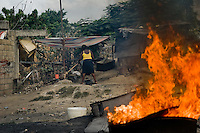A Haitian woman works in the aluminium recycling shop on the street of Port-au-Prince, Haiti, 11 July 2008.