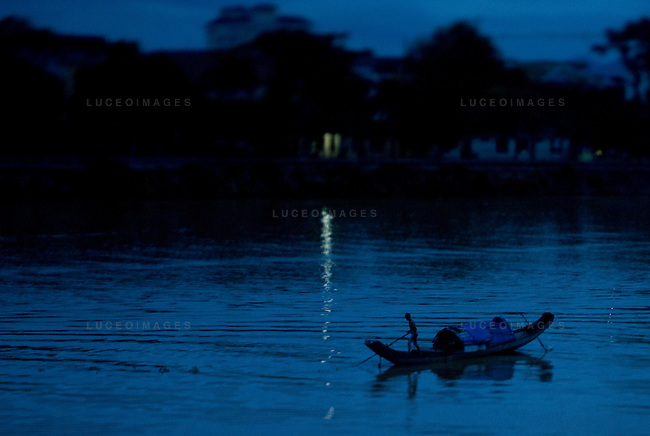A Vietnamese man fishes by moon light on his boat in Hue, Vietnam.