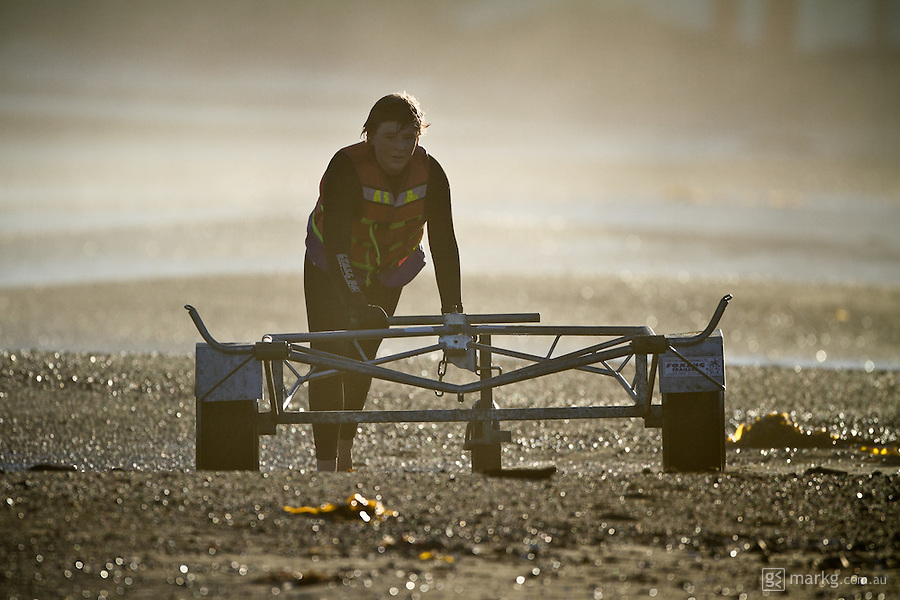 A member of the Lyall Bay SLSC pushes a trailer down the beach to pick up the IRB (inflatable rescue boat)