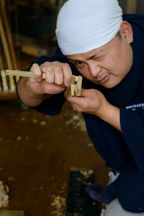 Keitarou Yokoyama checking the thickness of a piece of bamboo as part of the bow making process. Yokoyama Reimei Bowmakers, Miyakonojo, Miyazaki Prefecture, Japan, December 23, 2016. A handful of bowyers from the Kyushu city of Miyakonojo make over 90% of all the bows used in traditional Japanese archery. The bows are made from laminated bamboo and haze wood in process that consists of over 200 individual tasks. At over two meters from tip to tip the bows the longest used in the world.