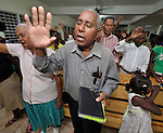 A man prays with raised hand in an evangelical church in La Hoya, a small rural town near Barahona in the southwest of the Dominican Republic. The service brings together Dominicans and Haitian-Dominicans from a nearby batey in an unusual demonstration of unity in a land where discrimination against Dominicans of Haitian ancestry is growing.