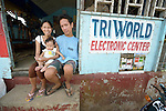 Marjo Lardera poses with his wife and child at the door to his electronics repair shop in Concepcion, Philippines. Lardera,  27, was born without arms but uses his feet and toes to earn a living repairing appliances and electronics. The town bore the brunt of Typhoon Haiyan, known locally as Yolanda, in November 2013. The storm damaged his house and killed one brother. Lardera is a member of the local People with Disabilities (PWD) group.