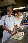 """Kenichi and Etsuko Yasuda, president and manager of Harumiya Co., prepare food for guests arriving for an evening aboard one of the family-run company's """"yakata-bune"""" pleasure boats in Tokyo, Japan on 31 August  2010. Photographer: Robert Gilhooly"""