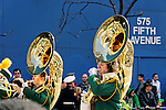 "MANHATTAN - MARCH 17: St. Patrick's Day Parade reflected on Tubas of High School Band marches up 5th Avenue, at E. 47th Street, NYC, on March 17, 2009. ""575 FIFTH AVENUE"" painted on blue construction wall in background. (glimpse of hat of someone in crowd in lower corner)  NOTE: Focus on reflections on tubas. Slight motion blur in marchers."