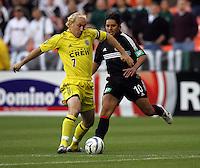 7 May 2005. Columbus' Simon Elliott (7) dribbles the ball away from DC United's Christian Gomez (10) at RFK Stadium in Washington, DC.