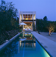 The steel and concrete structure of the house is surrounded with glass and in evening light appears to float above the long narrow swimming pool