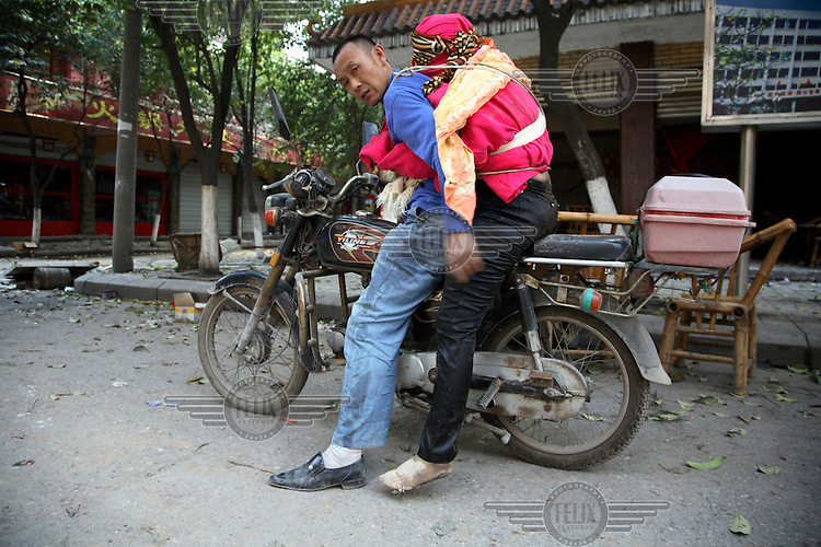 A man straps his dead wife onto him and his motorcycle. She was killed when an earthquake measuring 7.9 on the richter scale hit Sichuan on 12/05/2008.