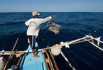 Nautilus hunting in a Philippine banca - an outrigger boat with 300 meter long rope for the nautilus traps.  Traps are let out in the late afternoon and picked up early morning the next day.  Floats with fisherman's flag declares ownership.
