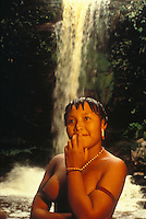 Portrait of young native Yanomami indigenous woman at waterfall, Amazon rain forest, Brazil.