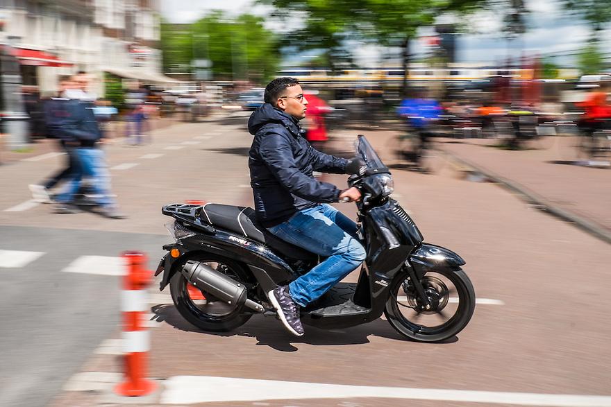 Nederland, Amsterdam, 30 mei 2015<br /> Snorscooter in het centrum van de stad.  Scooters stoten veel fijn stof uit en zijn enorm ongezond voor de stadsbewoners. De luchtkwaliteit wordt ernstig aangetast door scooters en bromfietsen of snorfietsn. Scooters irriteren veel verkeersdeelnemers omdat ze zich niet aan de verkeersregels houden en hard en a-sociaal rijden.<br />  <br /> Foto: Michiel Wijnbergh