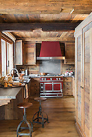 The wooden kitchen units appear to blend into the walls and ceiling around them and only the red range and its extractor stand out as contemporary elements in this rustic room