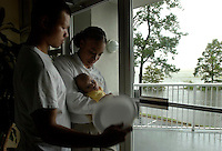 DAPHNE, ALA 8/29/05-Monique Boyd holds her daughter Kayla, age 4 months as father Craig Agualo, left, joins them watching Hurricane Katrina blow through Mobile Bay from inside the Hampton Inn, Monday in Daphne, Ala. COLIN HACKLEY PHOTO