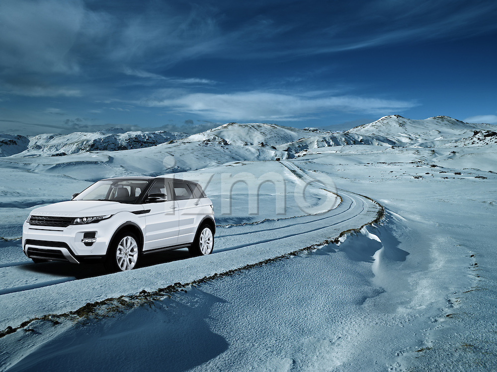 One white 2011 Land Rover Range Rover Evoque driving through deep snow in the mountains.