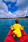 Boy kayaking on Hanalei Bay along the north shore, Island of Kauai, Hawaii USA