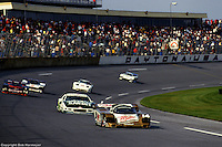 The Porsche 962 of Al Holbert, Derek Bell and Chip Robinson leads a group of cars through the Daytona tri-oval during the early laps of the 1988 race.