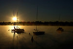 Sailboats rest in the calm and steamy waters of Lake Nokomis as the sun rises