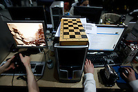 A chess board rest on top of a computer while its' owner is busy with more modern activities. One of the world's largest convention of computer enthusiasts, simply called 'The Gathering'. Over five thousand young people come together each Easter, some travelling long distances, each carrying their own computer equipment to the massive Vikingship sports hall in the city of Hamar. The main activity is online gaming. Many hardly see daylight or taste fresh air for the entire five days as they compete with their fellow geeks for cash prizes and the honour of being the best.