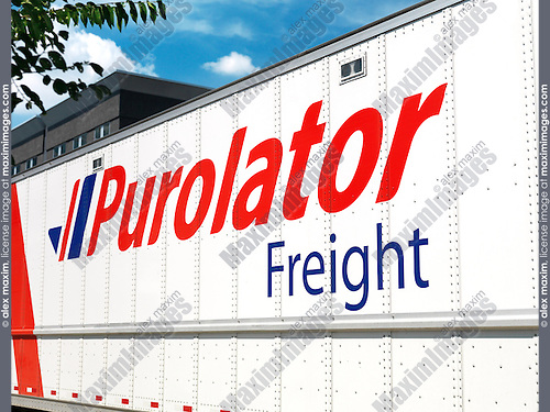 Purolator Freight truck over blue sky city background. Canada.