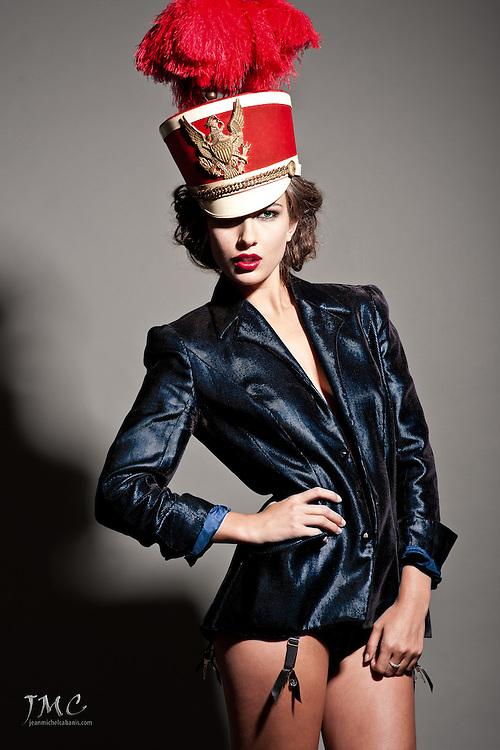Beautiful brunette fashion model in red hat, blue vest close-up