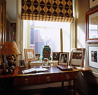 The writing desk in the study fits snugly in front of the sash window and displays a collection of framed photographs and prints