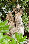 Sanur Beach, Bali, Indonesia; a winged dragon sculpture sitting on top of a stone wall along the beach boardwalk