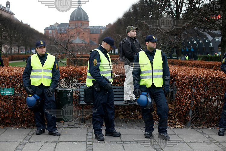 Police and a photographer wait during a demonstration in the centre of  Copenhagen. United Nations Climate Change Conference (COP15) was held at Bella Center in Copenhagen from the 7th to the 18th of December, 2009. A great deal of groups tried to voice their opinion and promote their cause in various ways. The conference and demonstrations was covered by thousands of photographers and journalists from all over the world...©Fredrik Naumann/Felix Features.
