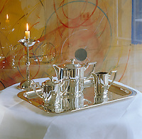 An abstract painting provides the backdrop for a polished silver tea set, tray and matching candle stick on a small side table