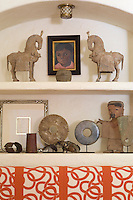 A collection of pre-Colombian artefacts displayed on  shelves set into an alcove