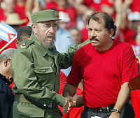 "Cuban President Fidel Castro (left) shakes hands wuith Daniel Ortega, Secretary of the ""Sandinista Front"" of Nicaragua, while observes the parade of May Day, Havana, Cuba, 2005. In the present year, the Cuban Government has made financial reforms trying to reactivate his economy. May 1, 2005.  Credit: Jorge Rey/MediaPunch"
