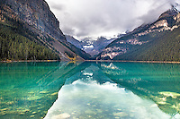 The layers of Lake Louise. Mountains, canyons and ridges make a nice layered effect reflection on the calm waters of the lake.  Lake louse is one of server al gems of the Canadian Rockies of Banff National Park in Alberta, Canada