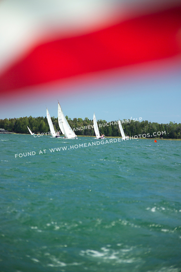 In the near distance, five ensign-class sailboats heel to a strong wind while racing on the port tack in this on-the-water image, while the ruffled edge of an American flag flutters in the extreme forground at the top of the frame to help set the scene for this summer image with plenty of room for text and design.
