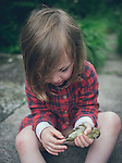 Close up of young girl outdoors holding a dead bird