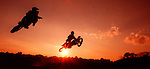 Two motor cross riders come off a jump as the sun sets in Tallahassee, Florida.    (Mark Wallheiser/TallahasseeStock.com)