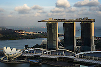 People party atop the Marina Bay Sands Skypark overlooking the Singapore skyline. The SkyPark, 200m above ground level, is larger than three football pitches and has an observation deck, 250 trees and a 150m infinity swimming pool. <br /> What does the future of cities look like? I explore Singapore and its continuous vertical development as it tries to balance the urban cityscape of sky scrapers with artificial nature by installing vast green walls. Photo by Suzanne Lee
