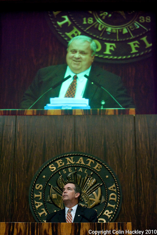 TALLAHASSEE, FLA. 3/2/10-OPENING DAY CH16-Senate President Jeff Atwater, R-Palm Beach Gardens, pauses as the Senate honors the late Sen. Jim King, R-Jacksonville, seen in the photo above him during the opening day of the legislative session, Tuesday at the Capitol in Tallahassee...COLIN HACKLEY PHOTO