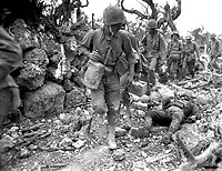 Marines pass through a small village where Japanese soldiers lay dead.  Okinawa, April 1945.  Norris G. McElroy.  (Marine Corps)<br /> Exact Date Shot Unknown<br /> NARA FILE #:  127-N-95-119485<br /> WAR &amp; CONFLICT BOOK #:  1231