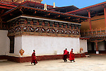 Asia, Bhutan, Punakha. Monks walking across Assembly Hall courtyard of Punakha Dzong.