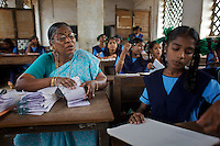 Staff and pupils at the Government Girls High School, Venugopalapuram, Cuddalore...Cuddalore's Government Girls High School is under-resourced with some student forced to sit on the floor for want of a desk. Though most classrooms are housed in a building that is only two years old, there is little ventilation to lessen the effects Cuddalore's tropical heat. The school does offer extra &quot;`bridge&quot; classes for those students recently arrived from village schools but staff are frequently absent from the school...Photo: Tom Pietrasik.Cuddalore town, Tamil Nadu. India.October 5th 2009