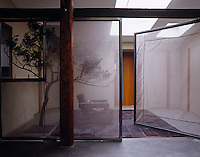 A pair of wire mesh doors screens off a single armchair and a tree sculpture