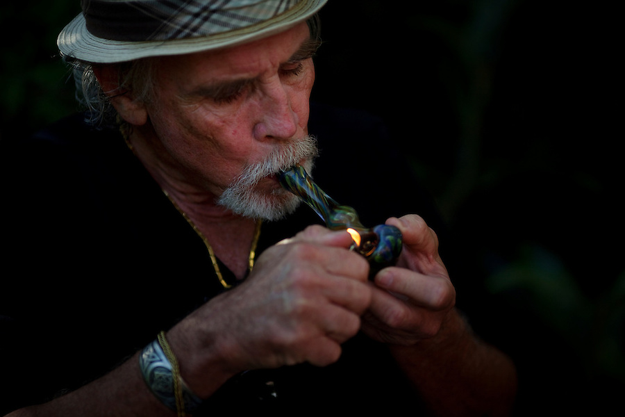 "Laguna Beach, California, October, 26, 2010 - Lonnie Painter lights up a pipe of marijuana at the home of his friend Bill Roley. Painter is the chairman and Roley is a member of the Laguna Woods for Medical Cannabis, a collective of about 100 members that operates as a dispensary for medical marijuana in the nearby senior community of Laguna Woods Village. Rolley was visiting with his friend Lonnie Painter who is the chairman of the Laguna Woods for Medical Cannabis. Up until this month, the members were allowed to grow marijuana within their own gardens. Painter says, ""We do this by the book, to the letter of the law. We are not potheads. We are people with legitimate medical needs."" Despite their best efforts, the group has faced some challenges recently. The board that oversees the community recently banned the growing of marijuana in the community gardens, despite the fact that each person has their own fenced and locked garden and the entire compound is surrounded by a chain-linked fence with barbed-wire. ""We can still grow indoors, but it costs 20 times as much,"" says Painter. California's Compassionate Use Act, passed in 1996, allows people with a prescription to use and cultivate medicinal marijuana.."