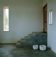 A pair of glass bowls has been placed beside the concrete steps in this minimal entrance hall
