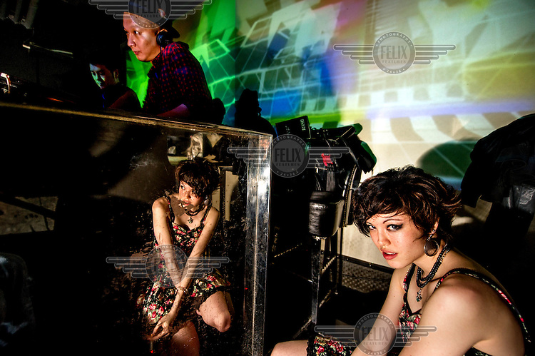 A young woman, sitting beside the DJ in a nightclub, smokes a cigarette.