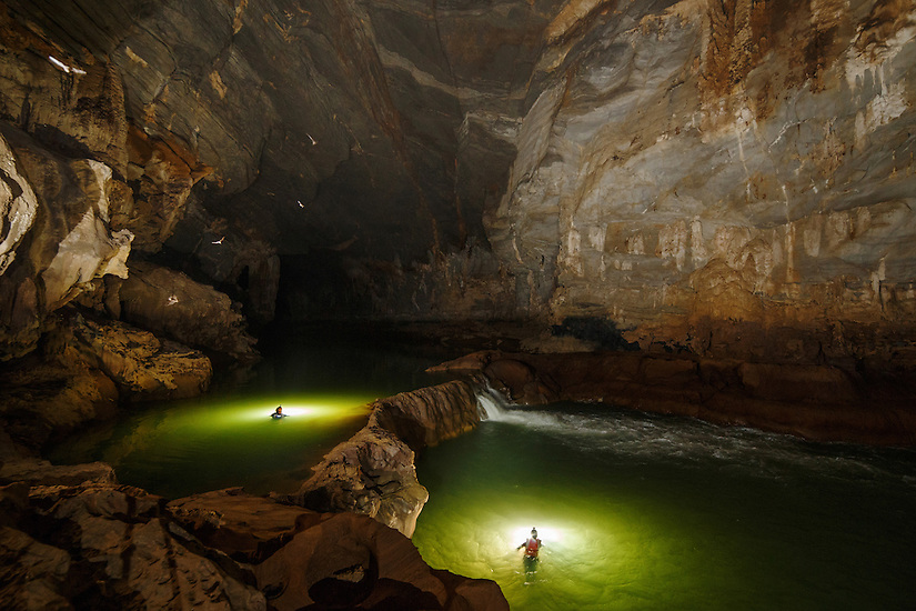 Cavers explore the Tu Lan river cave. There are multiple waterfalls in this section of the cave.
