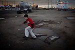 Ten-year-old Benito Tirjeron jumps over a puddle on the edge of the Parklawn neighborhood in Modesto, Calif., March 1, 2012. Across California there are hundreds of unincorporated communities like Parklawn. While a few are some of the state's richest areas; most lack sewer systems, clean drinking water, sidewalks, street lights, and storm drains. Populated by poor, working class Latinos, they're neglected by local government and lack the resources to install the most basic infrastructure that city residents rely on.<br />