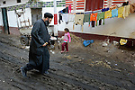 Father Joil Sobhe, a Coptic Orthodox priest, walks down the main street in Sakra, Egypt, as he visits church members.