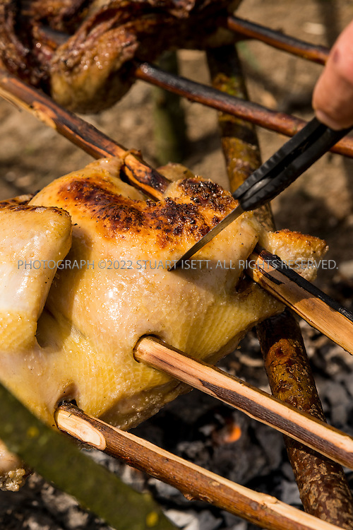 6/22/2015 &mdash; Everett, WA, USA<br /> <br /> Steven Rinella, an avid outdoorsman and hunter, cooks both wild duck and domesticated chicken over an open wood fire in Everett, WASH. <br /> <br /> Here Steven pokes the chickens's meat to see if it is cooked.<br /> <br /> Both birds were skewered with branches cut from nearby Alder trees and hung over the fire using more Alder branches.<br /> <br /> <br /> <br /> Photograph by Stuart Isett<br /> &copy;2015 Stuart Isett. All rights reserved.