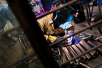 A bicycle welder works on a bike frame fixed on a welding jig in a small scale bicycle factory in Cali, Colombia, 27 June 2014. Due to the strong, vibrant cycling culture in Colombia, with cycling being one of the two most popular sports in the country, dozens of bike workshops and artisanal, often family-run bicycle factories were always spread out through the Colombian cities. However, growing import of cheap bicycles and components from China during the last decade has led to a significant decline in domestic bicycle production. Traditional no-name bike manufacturers are forced to close down their factories, struggling to survive in the competitive bicycle market.