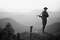 An All Burma Students' Democratic Front (ABSDF) soldier standing guard on a bunker in front of Elephant Mountain.